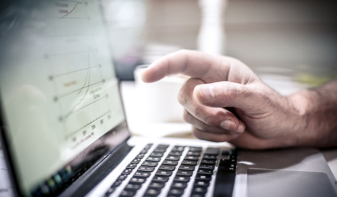 Close-up of a man's hand pointing at a laptop display of a graph
