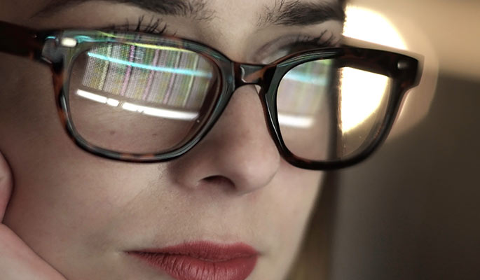 Close-up of a woman at a computer with graphs reflected in her glasses
